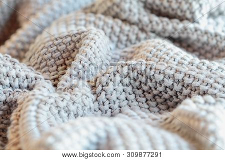 Abstract Of A Soft Knit Grey Throw Blanket With Selective Focus In Center