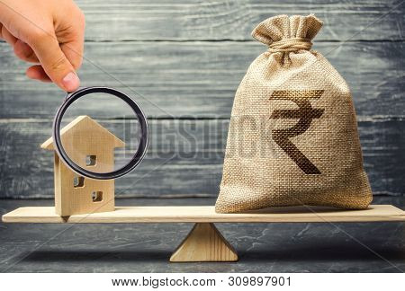 Money Bag With Indian Rupee (rupiah) And Wooden House On Scales. Fair Value Of Real Estate And Housi
