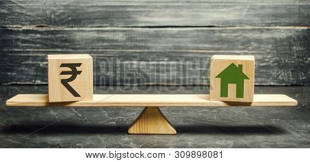 Money - Indian Rupee (rupiah) And Wooden House On Scales. Fair Value Of Real Estate And Housing. Pay