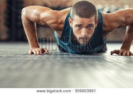 Young athlete doing push ups as part of bodybuilding training. Muscular guy doing a pushup on floor at fit gym. Determined athletic guy in sportswear exercising.
