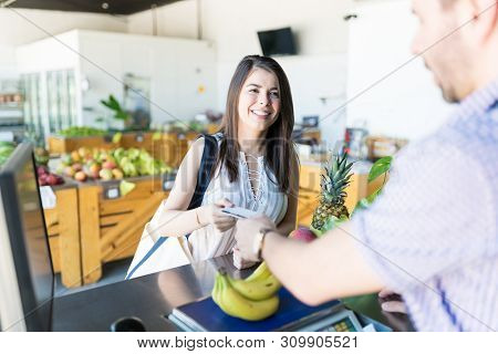 Gorgeous Caucasian Woman Using A Credit Card To Pay For Her Groceries At Store