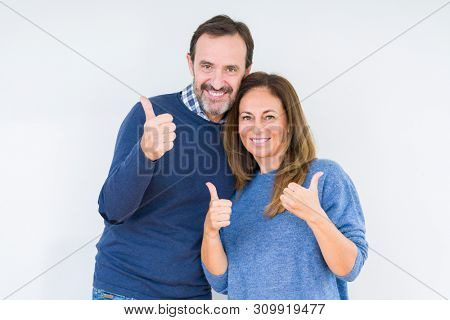 Beautiful middle age couple in love over isolated background success sign doing positive gesture with hand, thumbs up smiling and happy. Looking at the camera with cheerful expression, winner gesture.