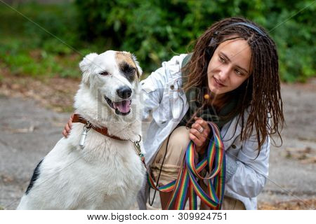 poster of The girl in the headphones next to the dog pooch on the background of blurred green. Latino girl of appearance with dreadlocks wearing a white jacket. Summer day. Communication with the animal.