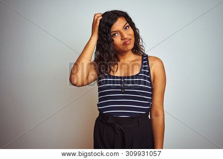 Transsexual transgender woman wearing striped t-shirt over isolated white background confuse and wondering about question. Uncertain with doubt, thinking with hand on head. Pensive concept.
