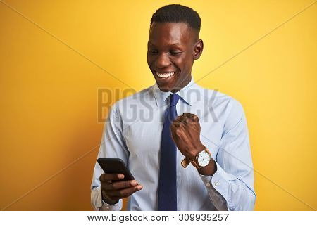 African american businessman using smartphone standing over isolated yellow background screaming proud and celebrating victory and success very excited, cheering emotion