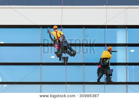 Two workers washing windows of the modern building