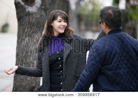 Female Pedestrian Walking Into A Friend By Coincidence On The Street.  They Are Meeting And Greeting
