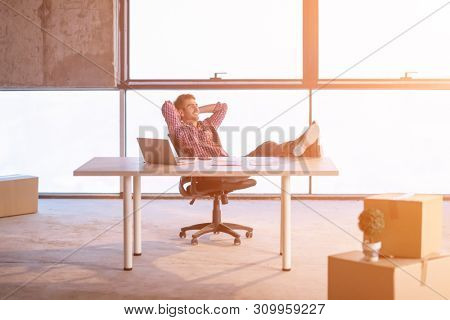young casual businessman taking a break on construction site while checking documents and business workflow using laptop computer with sunlight through the windows during moving in at new startup