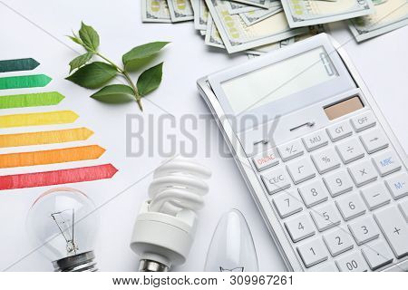 Composition With Energy Efficiency Rating Chart, Light Bulbs And Calculator On White Background