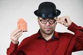 Adult man wearing funny hat and eyeglasses holding small red house model. Guy being real estate agent. Home ownership concept. poster