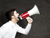 portrait of a young man shouting using a megaphone against a grunge wall poster