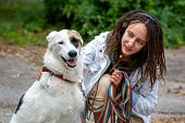 The girl in the headphones next to the dog pooch on the background of blurred green. Latino girl of appearance with dreadlocks wearing a white jacket. Summer day. Communication with the animal. poster