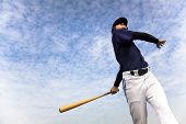 baseball player taking a swing with cloud background poster