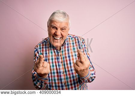 Senior handsome hoary man wearing casual colorful shirt over isolated pink background Showing middle finger doing fuck you bad expression, provocation and rude attitude. Screaming excited