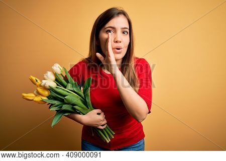 Young blonde woman holding romantic bouquet of tulips flowers over yellow background hand on mouth telling secret rumor, whispering malicious talk conversation