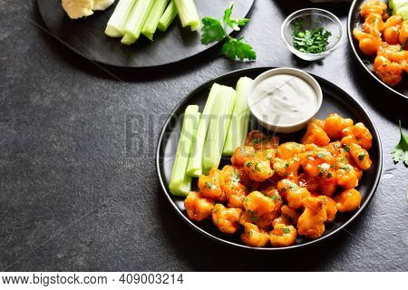 Cauliflower Buffalo Wings With Celery And Sauce On Plate Over Black Stone Background With Free Space