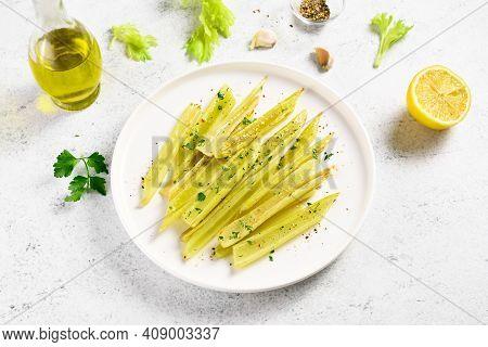 Braised Celery On Plate Over Light Stone Background.