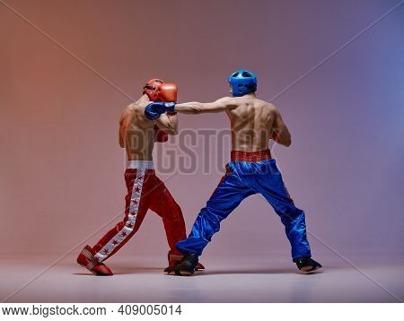 Wrestling Of Athletic Boxers Fighting Males In Helmets And Boxing Gloves In Red Light In Studio, Mar