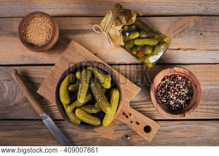 Homemade Canning. Marinated Cucumbers Gherkins With Dill And Garlic In A Glass Jar On The Wooden Tab