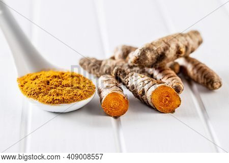 Indian turmeric powder and root. Turmeric spice. Ground turmeric on white table.