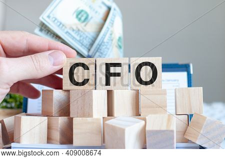 The Word Cfo On The Wooden Blocks And A Bank With Money In The Background, Business Concept. Cfo - C