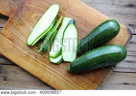 Sliced Zucchini On A Round Wooden Cutting Board. Close-up Of Fresh Young Squash With Water Drops. Or
