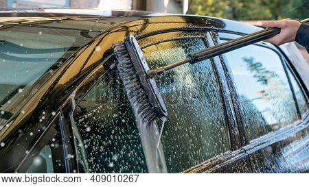 Outdoor Car Washing With A Soapy Brush. Car Window Detail Washing With A Foam.outdoor Activities.