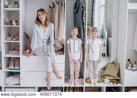 Female Wardrobe. Stylish Mother, Cute Twin Daughters Wearing Comfortable Home Clothes Posing In Clos