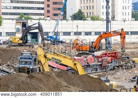 Excavators And Other Equipment Are Demolishing The Old Building. Heavy Construction Equipment In A P