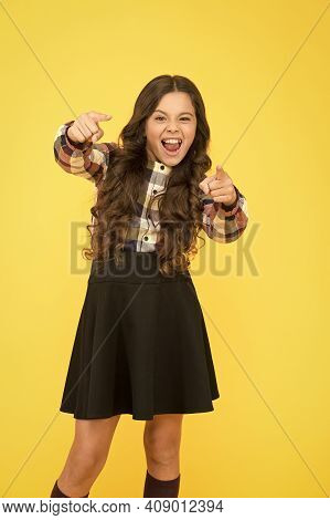 Get More. Excited Girl Pointing Straight Yellow Background. Little Child Wear School Uniform. Back T