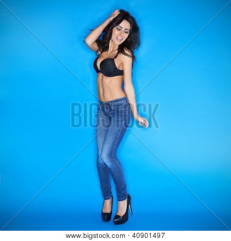 Happy sexy party woman with a vivacious smile and beautiful body dancing and jiving in tight fitting jeans and stilettoes on a blue background
