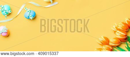 Easter Background. Colorful Egg With Tape Ribbon, Spring Tulips, Feathers On Pastel Yellow Backgroun