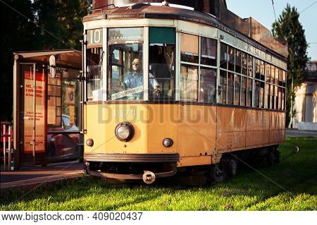 Yellow Tram In Retro Style Stands Near Tram Stop. Famous Vintage Tram In Downtown Of Milan On Sunny