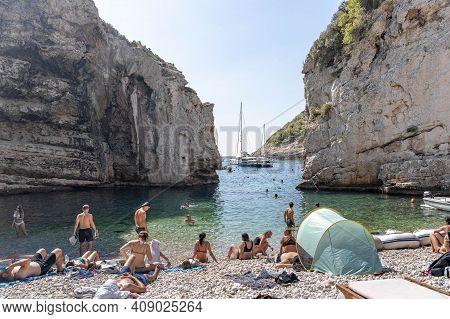 Vis, Croatia - Aug 17, 2020: Tourists Sunbathing On Sheltered Cove Stiniva Beach In Summer