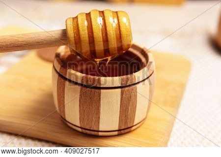 Wooden Stick Above Jar With Aromatic Natural Organic Honey. Jewish New Year Healthy Holiday Concept.