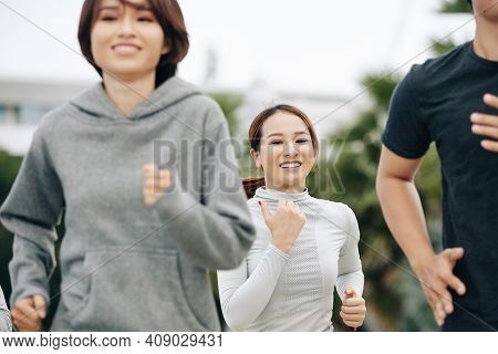 Beautiful Young Fit Woman Smilng At Camera When Jogging Outdoors With Her Friends