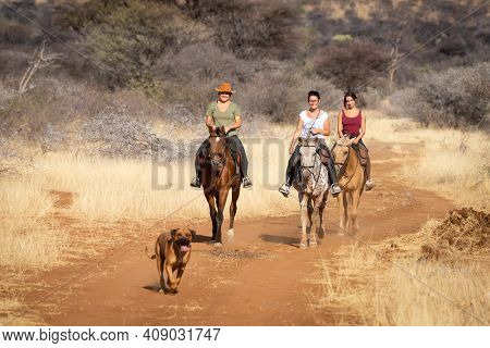 Three Women Ride Along Track With Dog