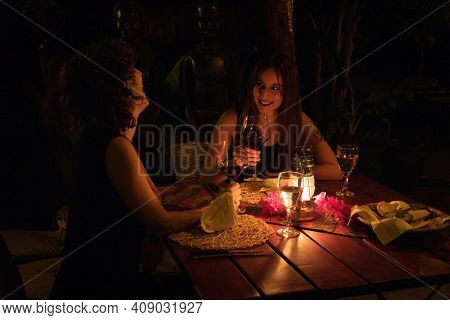 Two Brunettes Drink Wine At Dinner Table