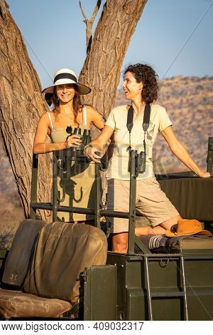 Two Female Guests Stand Laughing In Jeep