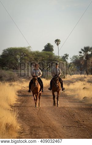Two Horsewomen Ride Side-by-side Along Dirt Track