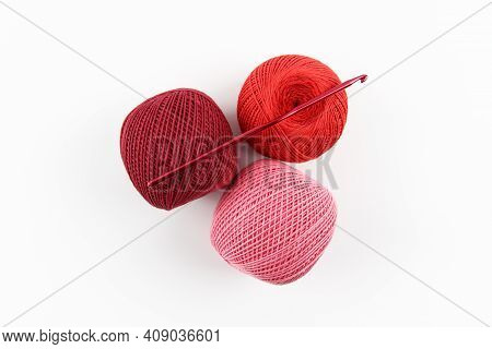 Crimson, Red And Pink Balls Of Cotton Thread And A Crochet Hook On A White Background. The Concept O