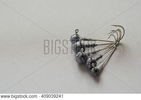 Various Jig Heads On A Light Background. A Special Device For Catching Predatory Fish With A Lead An