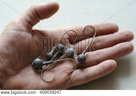 Various Jig Heads Lie In An Open Male Palm. A Special Device For Catching Predatory Fish With A Lead