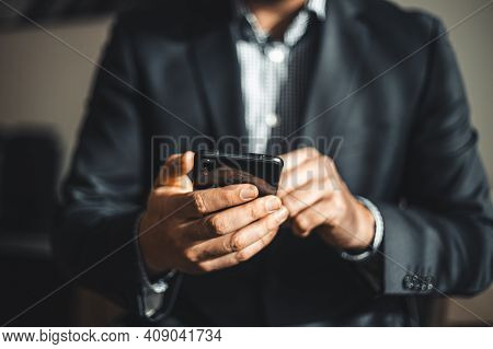 Close Up View Of Hand With Mobile Phone. Businessman In Suit Holding The Cell Phone