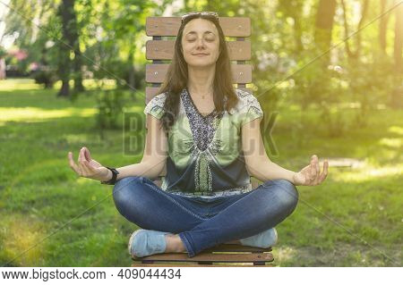 Young Girl Doing Yoga And Meditating In The City Park On A Sunny Day. Sitting On A Wooden Bench. Ton
