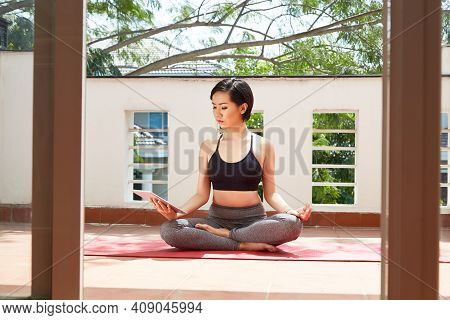 Serious Calm Fit Woman Sitting On Yoga Mat In Lotus Position And Watching Video N Meditation On Tabl
