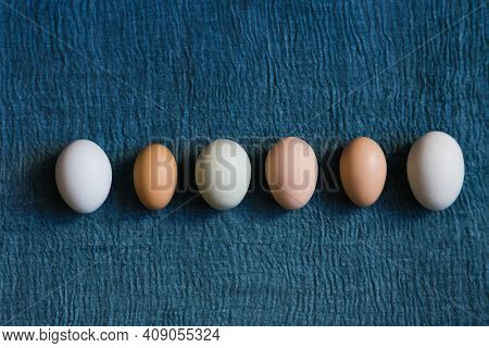 Organic Chicken Eggs Of Different Calibers On Blue Textile Background.