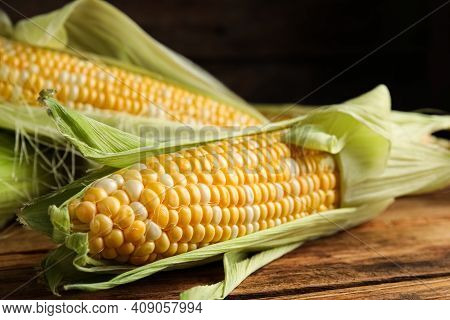 Tasty Sweet Corn Cobs On Wooden Table, Closeup
