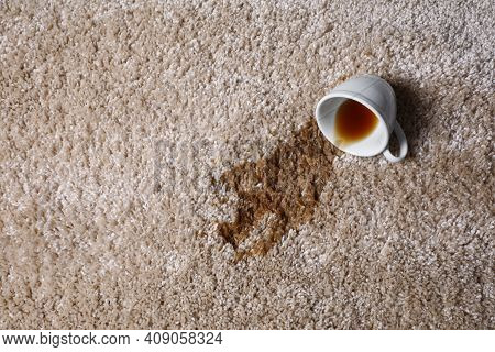 Overturned Cup And Spilled Tea On Beige Carpet, Top View. Space For Text