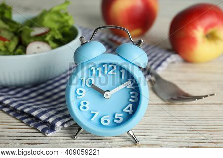 Alarm Clock And Healthy Food On White Wooden Table, Closeup. Meal Timing Concept